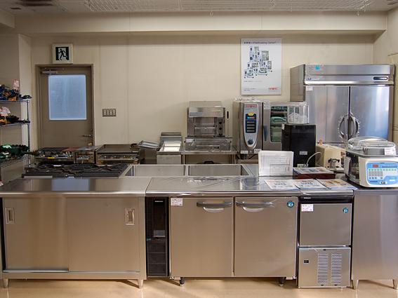 配置はオーソドックスなアイランド方式(作業スペースを中央に配置)で、台下冷蔵庫、製氷機、シンクなどを置いてます。壁側は縦型冷蔵庫、焼台など置き、ラショナル社のスチームコンベクションオーブンを中央右に置いてます。