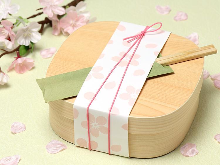 春らしいラッピングに、ちらし寿司やお饅頭などを入れてご使用いただくのもおすすめです。※掛紙は新発売の「07-15302-588 帯紙 さくらさくら」を使用しています。
